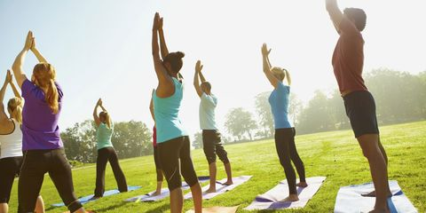Group yoga outside in park on a sunny day