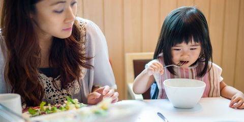 Toddler eating in a restaurant with mother