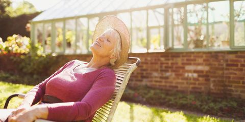 Older woman sat outside sunbathing