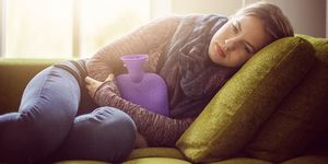 Girl on sofa with hot water bottle cold