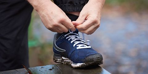 Cropped shot of male runners hands tying trainer laces on park bench