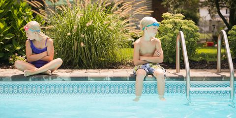 Sister and brother siblings arguing in swimming pool