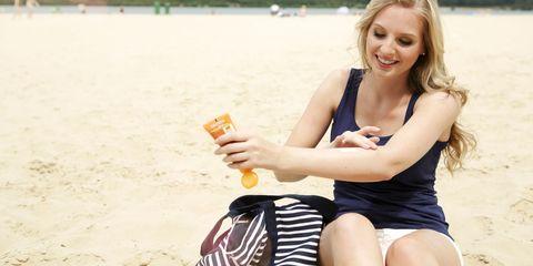 woman sitting on the beach using suncream