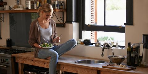 Woman eating salad sat on side in kitchen