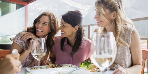 Middle aged women eating together in restaurant