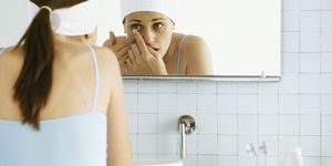 Woman standing in front of bathroom mirror inserting contact lens