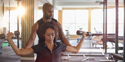 Personal trainer helping woman with dumbbells