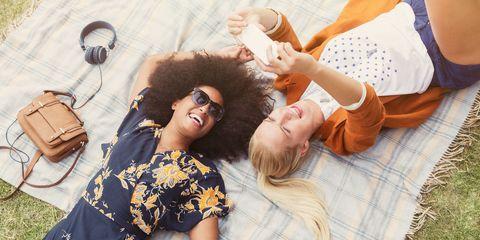 Friends taking selfie relaxing on blanket in grass