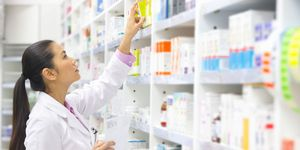 Pharmacist, holding prescription, looking for medication on pharmacy shelf