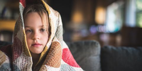 Sick girl wrapped in blanket