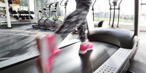 Woman's legs running on treadmill in gym