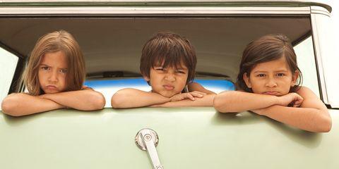 Three sullen children in back of estate car