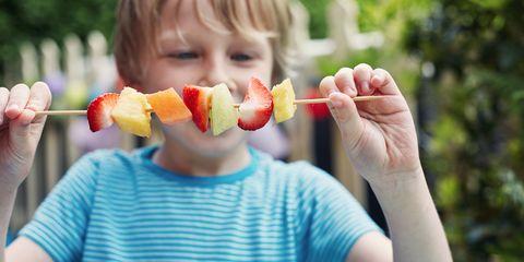Child eating fruit kebab