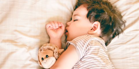 Boy sleeping on bed holding a soft toy by his side