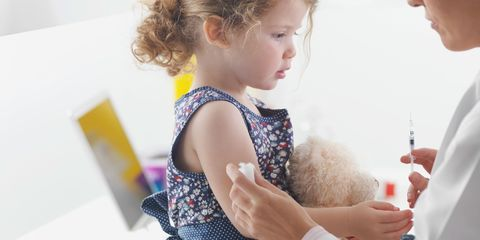 Doctor giving toddler girl a vaccination