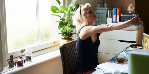 Young woman stretching arms at desk in home office
