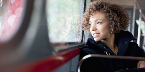 Woman on bus journey smiling
