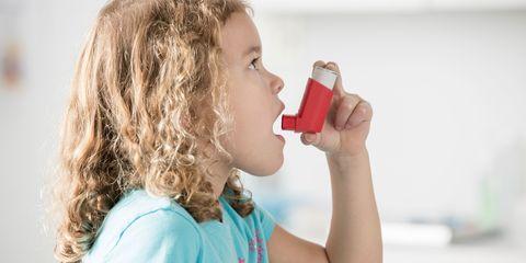 girl using inhaler in doctor's office