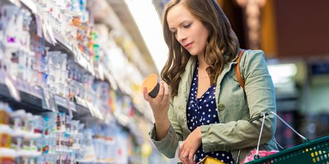 Woman reading healthy food labels at supermarket