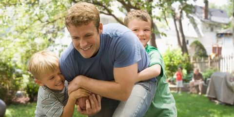 Father playing with sons outside