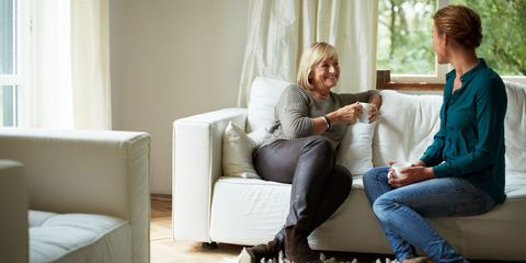 Mother and daughter having coffee on sofa