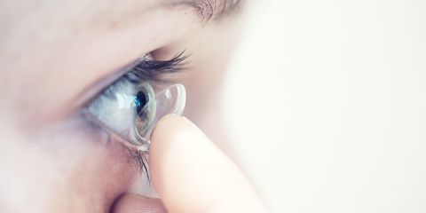 Woman putting contact lens in