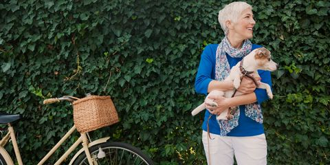 Happy older woman with dog and bicycle