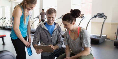 Personal trainer with clipboard talking to women gym