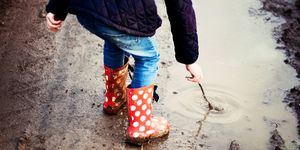 Child playing in muddy puddles