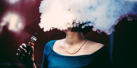 Femme fumant vaping e-cigarette