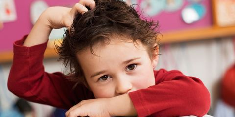 Child scratching head head lice