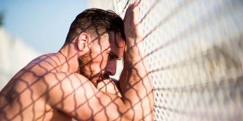 Athlete leaning against fence