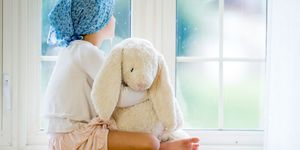 Young patient with cancer holding bunny rabbit toy