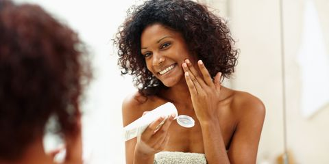 Woman applying skincare product in mirror