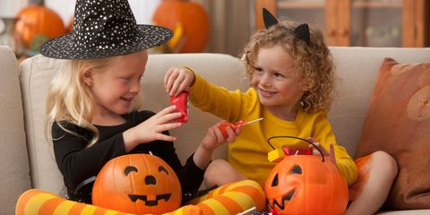 Two young girls at halloween eating sweets from plastic pumkins