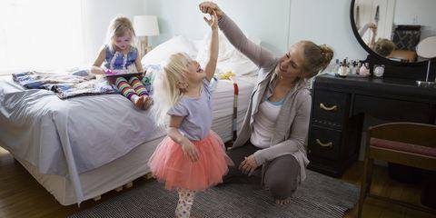 Mother spinning daughter in tutu in bedroom