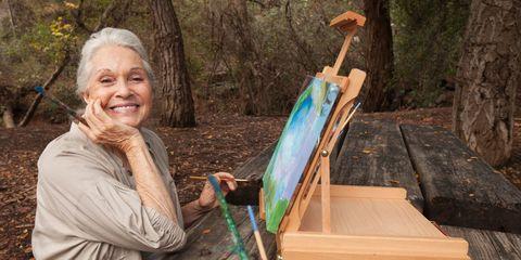 Older Caucasian woman painting in park