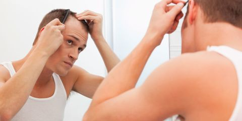 Man combing hair in front of mirror