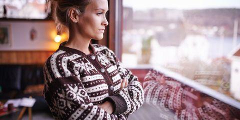 Woman in winter jumper looking out of winter