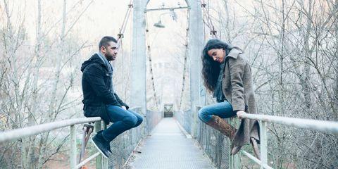 Unhappy couple sitting on a bridge