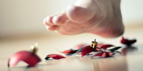 Bare foot over broken Christmas bauble