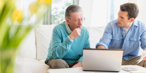 Senior father and son talking sat down with laptop