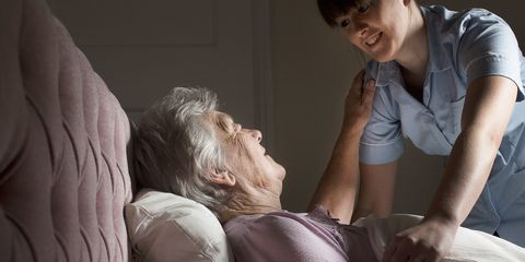 Personal care assistant chatting to senior woman in bed