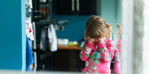 Reflection of upset girl rubbing eyes in mirror