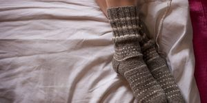 Feet in wollen socks on bed
