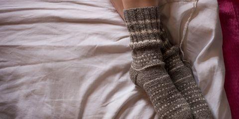 Feet in wollen socks on bed