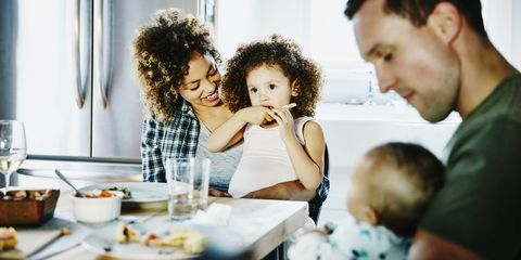 Mother holding daughter while family dines