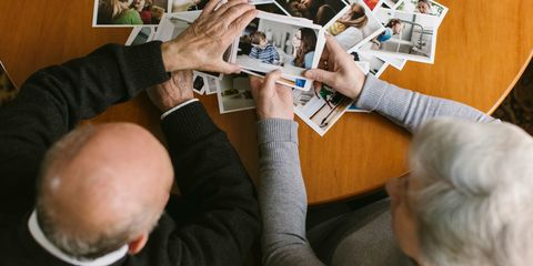 Elderly man and woman couple looking at old photographs