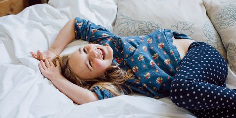Young girl lying on bed smiling