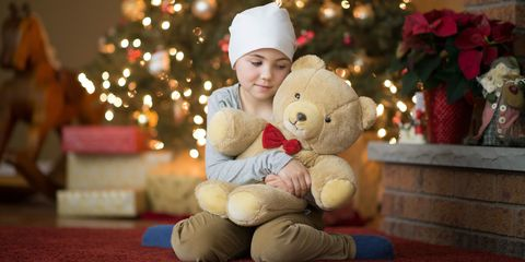 Little girl with cancer at Christmas time holding a teddy